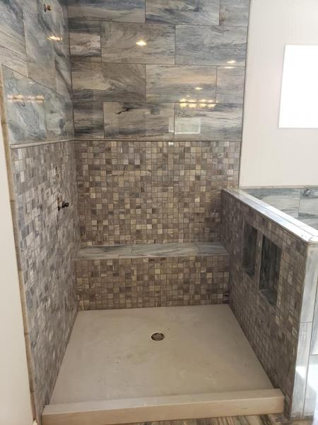 The tile on the walls are Happy Floors, Citrus 12x24 color: Ocean in the polished finish, the 2x2s to match underneath and the pencil in between and on the edges are Shaw, Pearl 1/2x12 color: Blue Grigio. Finishing with the marble pan in color: Platinum White.